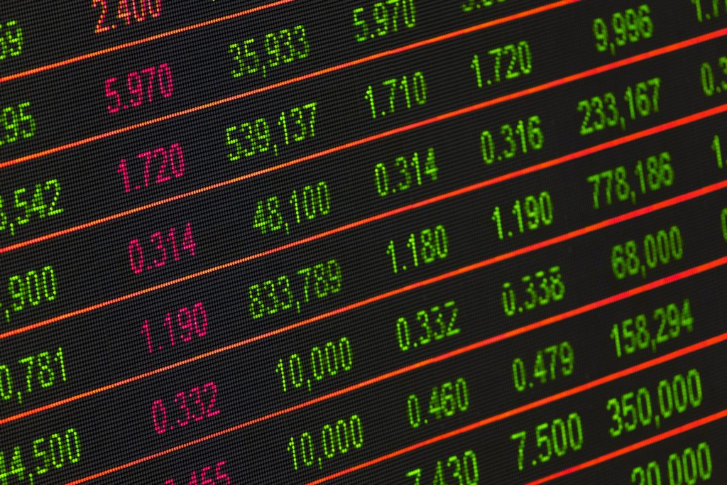 red and green electronic numbers on a screen, showing stock prices and their movements